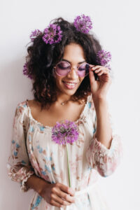 Adorable african girl with curly hairstyle holding allium. Studio shot of black lady in sunglasses posing with purple flowers.
