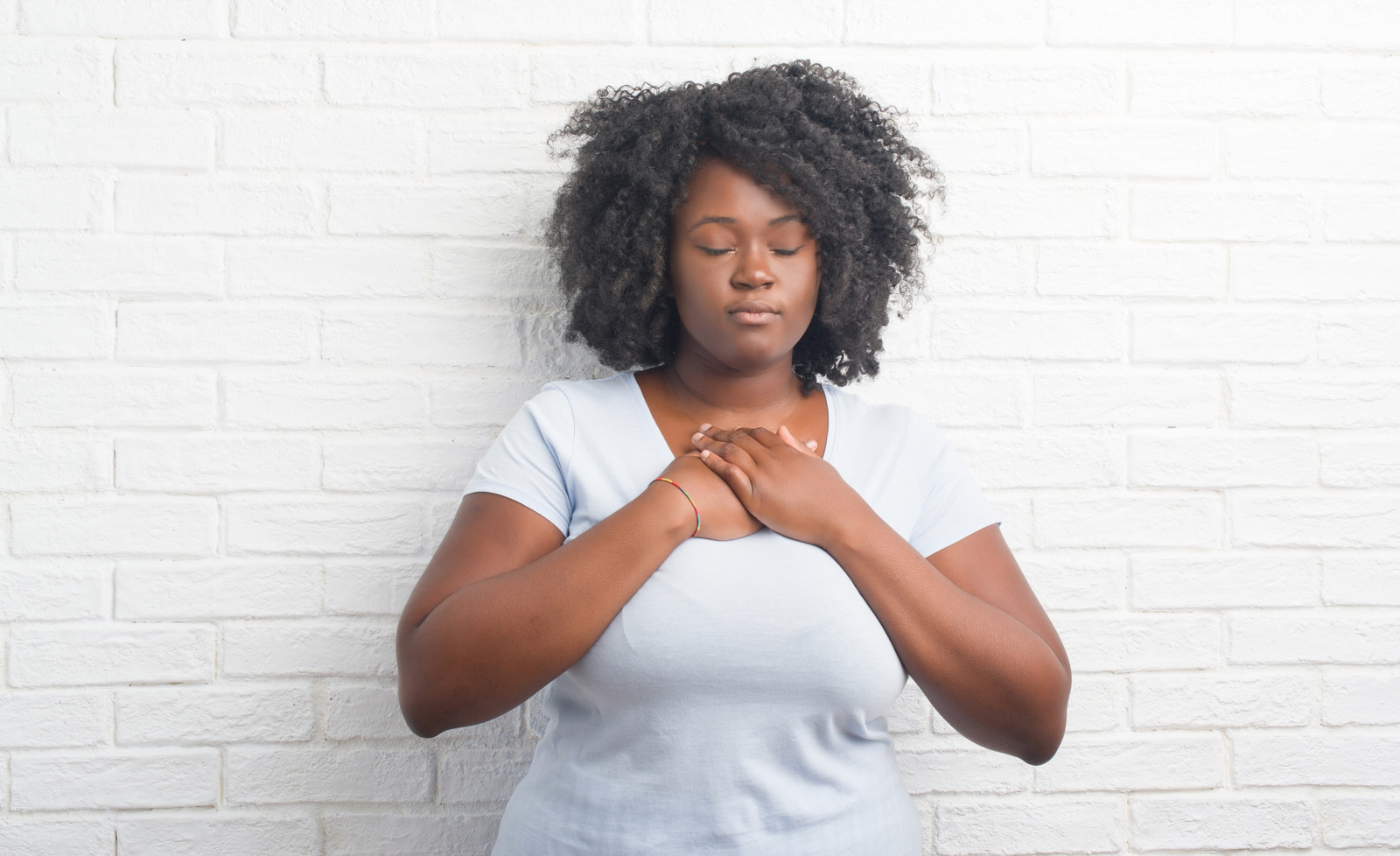 Young african american plus size woman over white brick wall smiling with hands on chest with closed eyes and grateful gesture on face. Health concept.